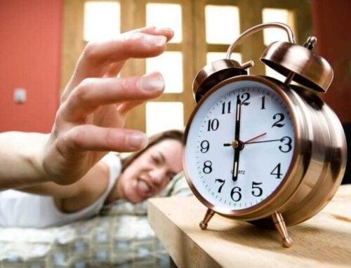 Öfkeli bir şekilde saatinin alarmını kapatan bir kadın.