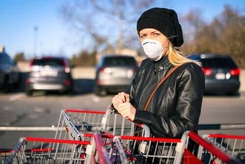 Alışveriş arabalarının önünde duran maske takmış bir kadın.