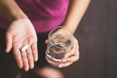 bir eilnde ilaç, diğer elinde bir bardak su tutan kadın