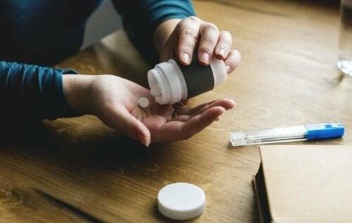 bir ilaç kutusundan avucuna ilaç döken kişi