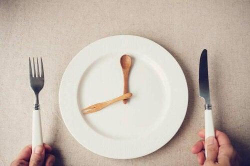 boş tabağının başında yemek saatini bekleyen aralıklı oruç uygulayıcısı