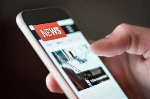 Cep telefonunda haberleri okuyan bir kişi.