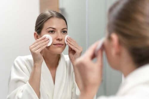 cildini temizleyen kadın pamukla
