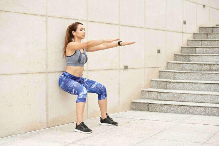 sırtını duvara dayayarak squat yapan genç sporcu