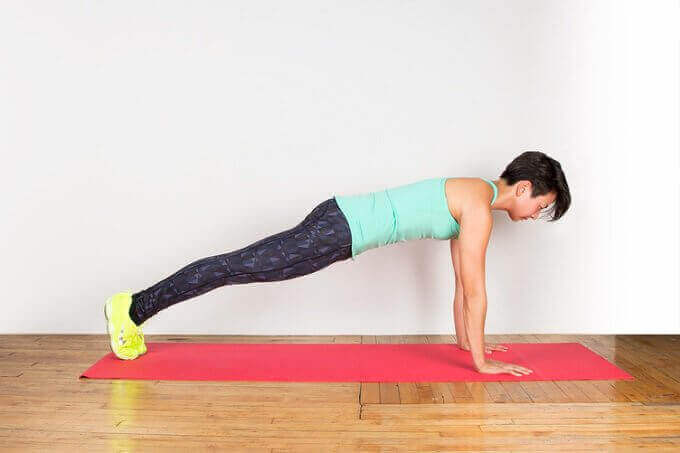 evinden çıkmadan formda kalmak için salonuna serdiği matın üzerinde plank yapan kadın