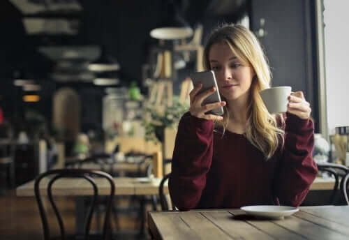Telefonuna bakarak kahve içen bir kadın.