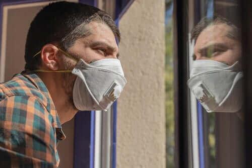 Karantina sırasında maske takmış camdan dışarı bakan bir adam.