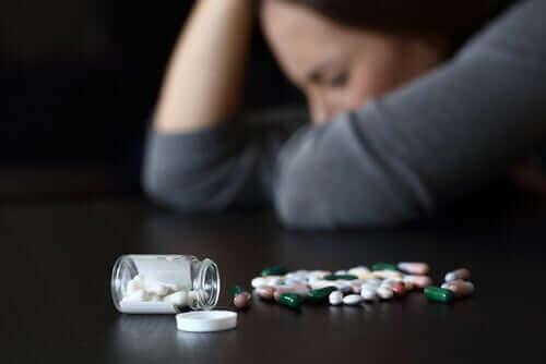 masa üstünde ilaçlar ve uyuklaya kadın