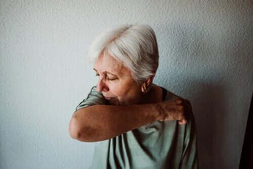 Dirseğinin içine doğru öksüren yaşlı bir kadın.