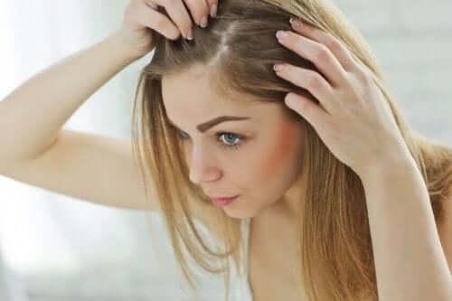 Saçlarının köklerine bakan bir kadın.