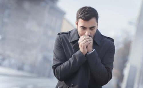 soğuk hava ellerini ısıtmaya çalışan adam