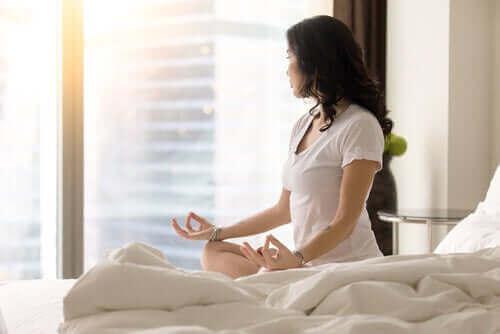 Yatağında oturmuş meditasyon yapan bir kadın.