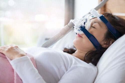 CPAP makinesine bağlı bir şekilde uyuyan kadın