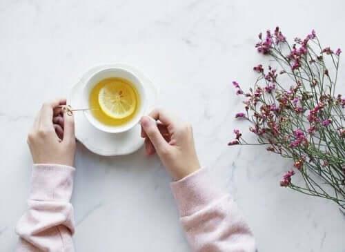 masada limon çayı ve çay fincanını tutan eller