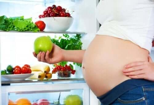 Elinde bir elma tutan hamile bir kadın.