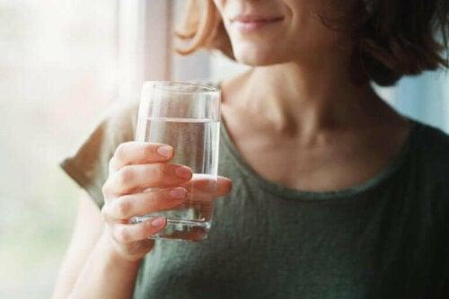 elinde bir bardak su tutarak gülümseyen kadın