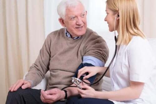 nurse measuring old man blood pressure