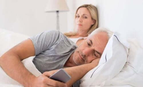 yatak çift telefonuna bakan adam