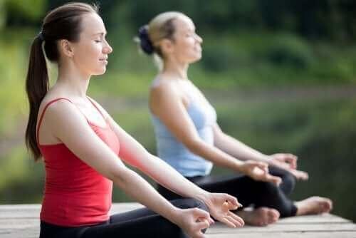 Dışarıda yoga yapan iki kadın.