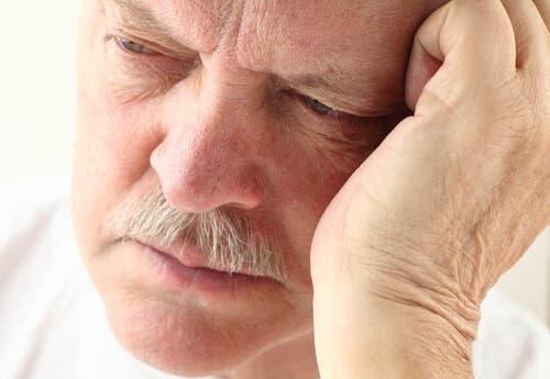 Başını eline dayamış yaşlı bir adam.