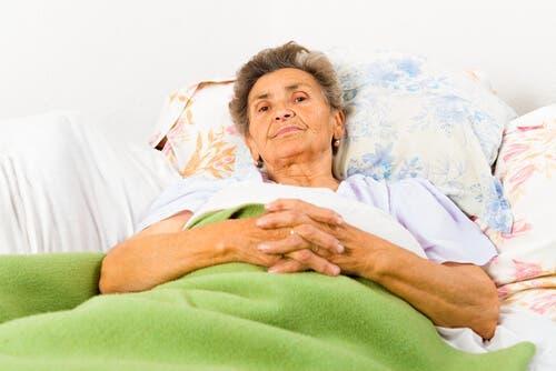 Azheimer hastalığı olan, yatağında uyanık yatan yaşlı bir kadın.