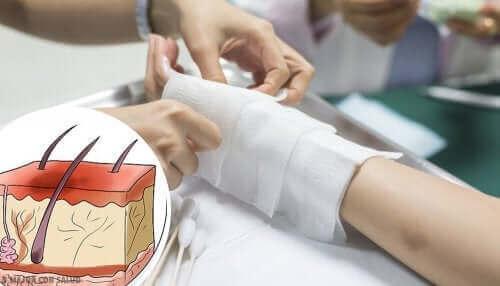 Bir kişinin bandajını değiştiren bir doktor.