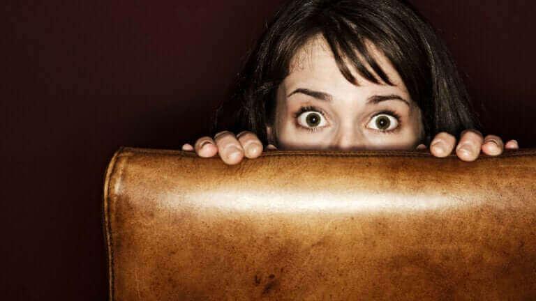 Kahverengi deri koltuğun arkasına saklanmış kanserden korkan kadın