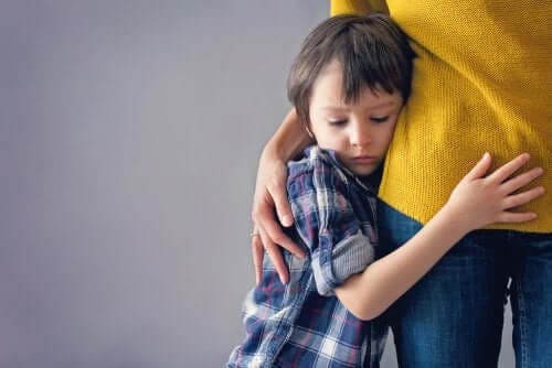 Korkuyla annesine sarılmış bir oğlan çocuğu.