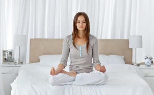 Yatağının üzerinde meditasyon yapan bir kadın.