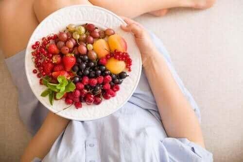 Meyve ve sebze yiyen hamile bir kadın.