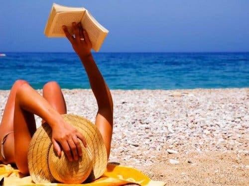 Plajda güneşlenerek kitap okuyan bir kadın.