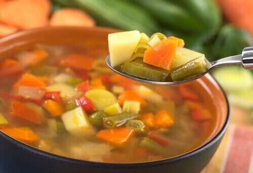 Sebze çorbasından bir kaşık alan bir kişi.