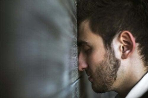 Yüzünü duvara dayamış bir kişi.