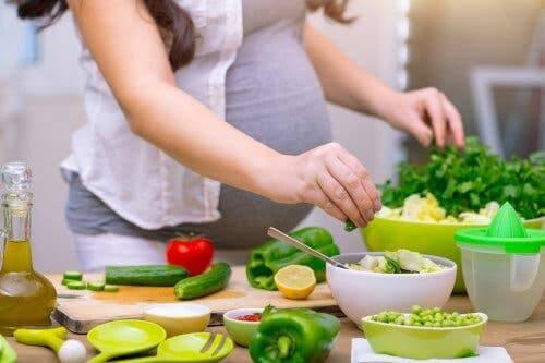 Salata hazırlayan bir hamile kadın.