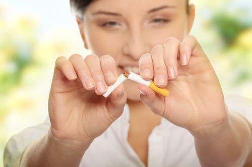 Elindeki sigarayı kıran bir kadın.
