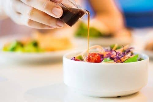 Salatasının üstüne sos döken bir kişi.