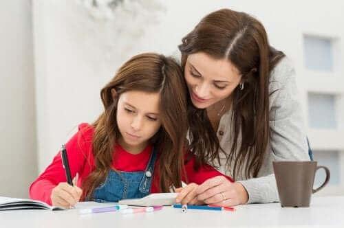 Çocuğuna ödevlerinde yardımcı olan bir anne.