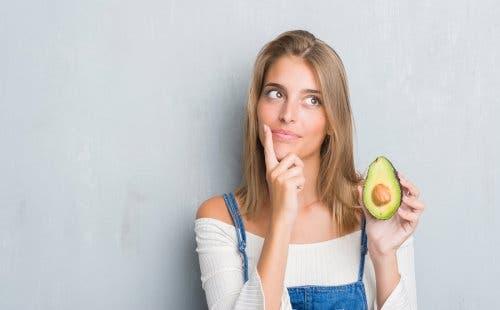 Elinde yarım avokado tutan bir kadın.