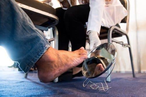 Aynada ayağını kontrol eden bir diyabet hastası.