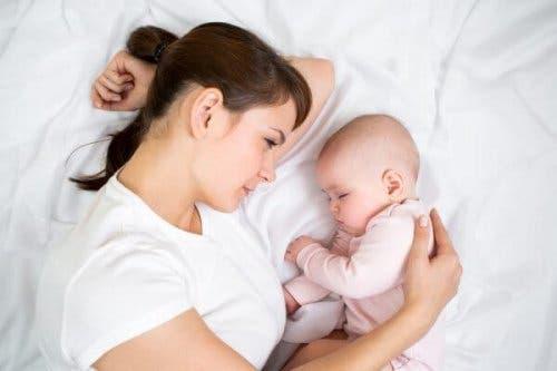 Bebeğinin yanına yatmış, onu izleyen bir anne.