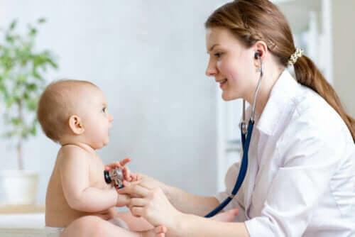 Bir bebeği muayene eden bir doktor.