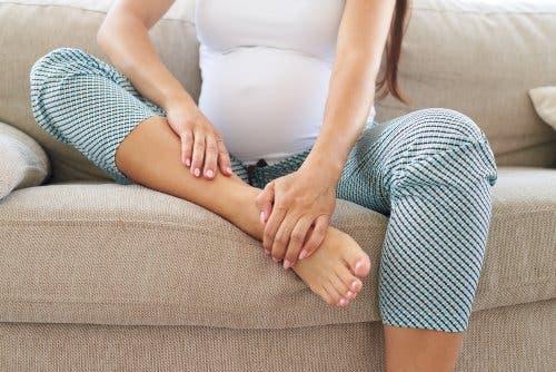 Ayaklarını ovan bir hamile kadın.