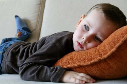 Kanepede yatarak bir şeyler izleyen bir oğlan çocuğu.