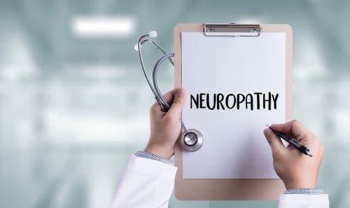 Üzerinde nöropati yazan bir kağıt olan bir kağıt altlığı tutan doktor.