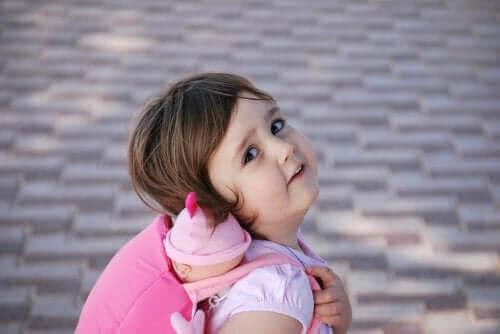 Oyuncak bebeğini sırtında taşıyan bir kız çocuğu.