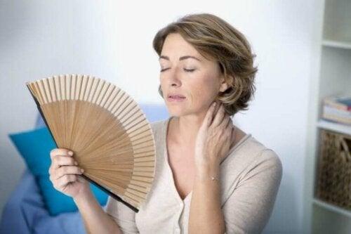 Perimenopoz semptomları deneyimleyen bir kadın.