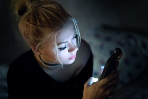 Gecenin karanlığında cep telefonunu kullanan bir kadın.