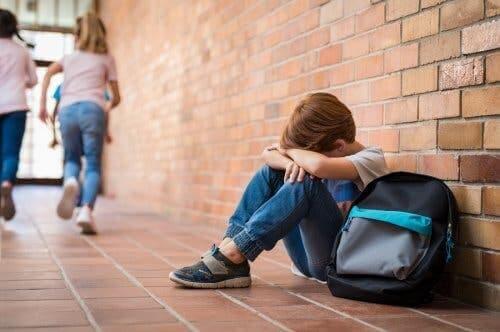 Koridorda yalnız başına oturan bir çocuk.