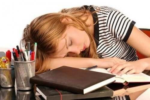 Önündeki kitapların üzerinde uyumuş yorgun bir kadın.