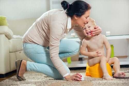 Yanında annesi ile tuvaletini yapan bir bebek.